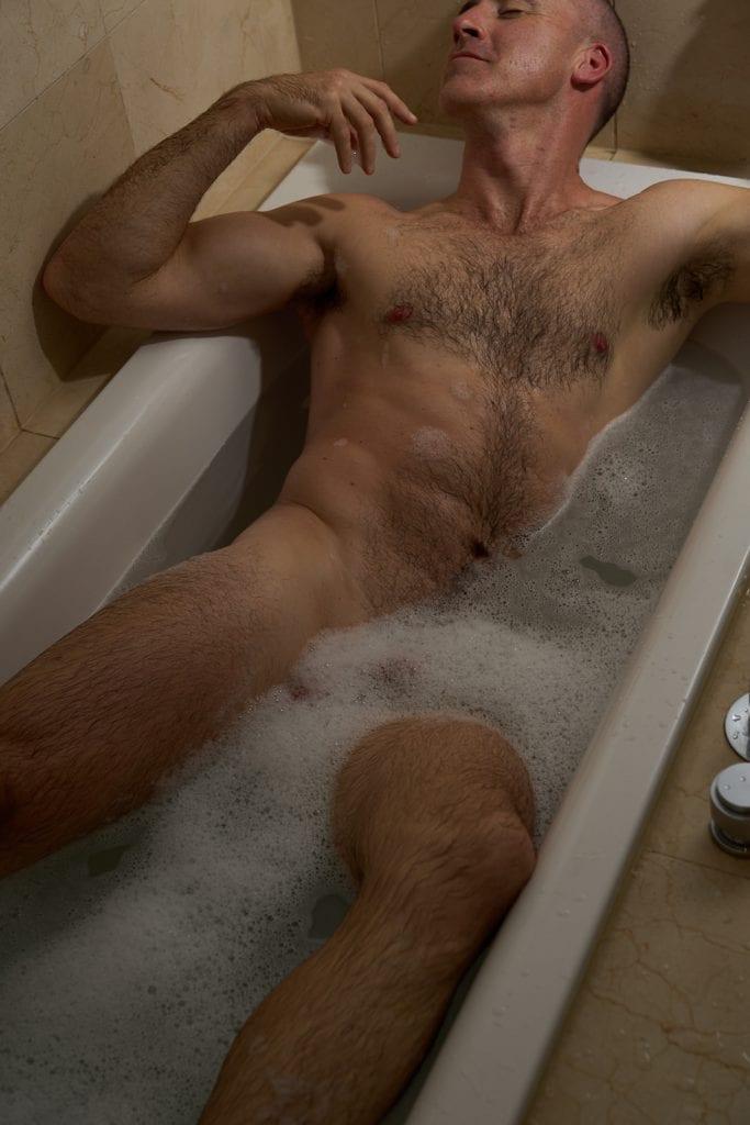 melbourne male escort in a bubble bath stoking his chin